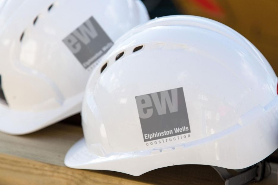 White safety helmet with elphinston wells grey logo on the side