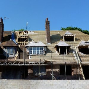 Large victorian building with all roof tiles removed and being replaced