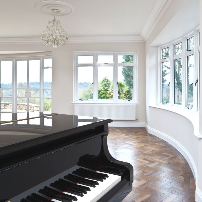 Room with piano in the foreground and large glass windows showing views across green hills