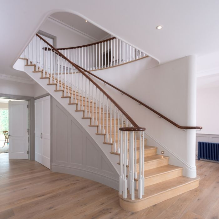 Large white living area with wooden staircase in centre of room