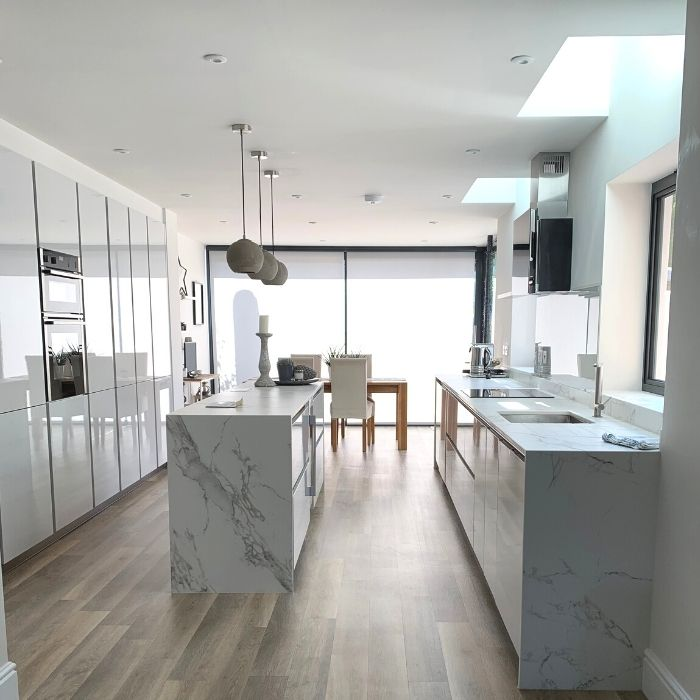 Side view of modern kitchen with wooden floor, marble worktop, white walls and square windows.