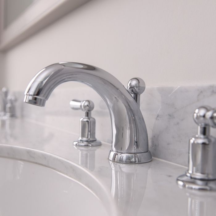 Close up of stainless steel taps mounted onto marble work top