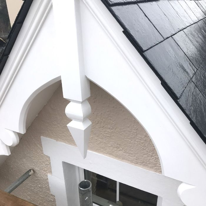White wooden roofing lintel with dark slate grey roofing tiles.