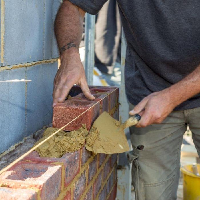 Builder laying bricks on an external wall