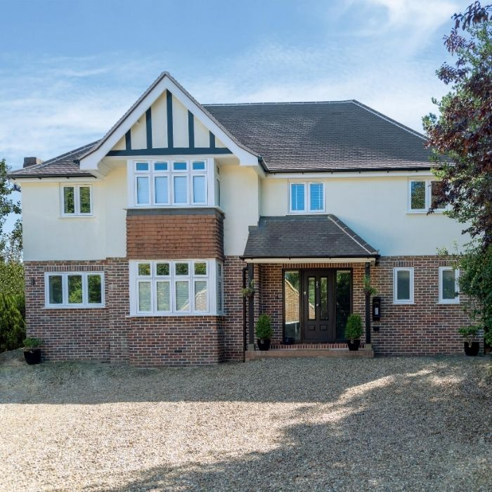 Large detached house with roof beams and gravel driveway