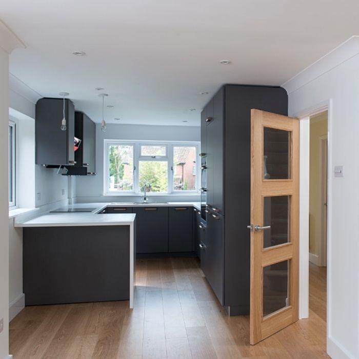 Kitchen with wooden flooring, modern tall, dark cupboards with white work surface.